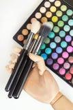 Mano con los cepillos del maquillaje, maquillaje colorido del maniquí Fotografía de archivo libre de regalías