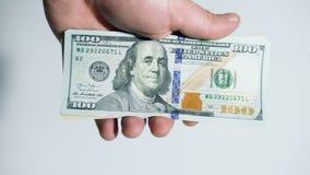 Mano con los d?lares americanos en un fondo blanco El hombre deja el dinero fuera de la mano almacen de video