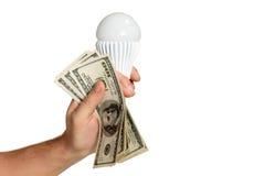 Mano con los dólares y la lámpara llevada Imagenes de archivo