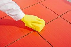 Mano con los guantes amarillos y los azulejos limpios de la esponja Fotos de archivo libres de regalías