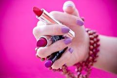 Mano con los lápices labiales, el nailpolish púrpura y las pulseras Imágenes de archivo libres de regalías