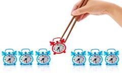 Mano con los palillos y el reloj de alarma Foto de archivo libre de regalías