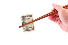 Mano con los palillos y los billetes de banco de dólar americano Imágenes de archivo libres de regalías