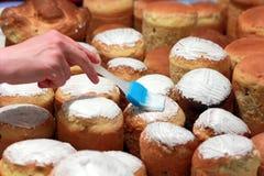 Mano con los panes del cepillo de un pan de la formación de hielo Foto de archivo libre de regalías