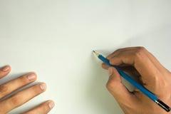 Mano con scrittura della matita sul fondo bianco, spazio libero Fotografie Stock