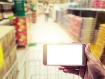 Mano con smartphone encendido borrosa en fondo de la alameda de compras Imagenes de archivo
