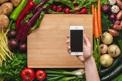 Mano con Smartphone sopra il fondo organico fresco delle verdure immagini stock libere da diritti