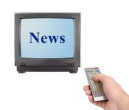 Mano con telecomando e notizie della TV Fotografia Stock