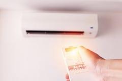 Mano con teledirigido dirigido en el sistema de aire del acondicionador Foto de archivo libre de regalías