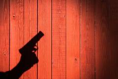Mano con un arma en una cerca de madera Fotos de archivo