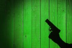 Mano con un arma en una cerca de madera Imagen de archivo