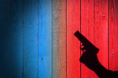 Mano con un arma en una cerca de madera Imagen de archivo libre de regalías
