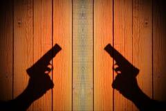 Mano con un arma en una cerca de madera Foto de archivo