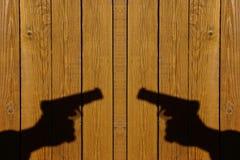 Mano con un arma en una cerca de madera Imagenes de archivo