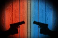 Mano con un arma en una cerca de madera Fotografía de archivo libre de regalías