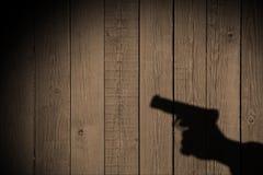 Mano con un arma en una cerca de madera Foto de archivo libre de regalías