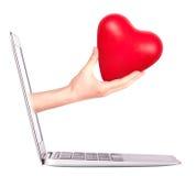 Mano con un cuore - regalo e computer portatile Immagini Stock