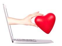 Mano con un cuore - regalo e computer portatile Fotografia Stock
