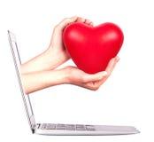 Mano con un cuore - regalo e computer portatile Immagini Stock Libere da Diritti