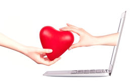 Mano con un cuore - regalo e computer portatile Fotografie Stock