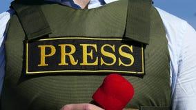 Mano con un micrófono en el fondo de un chaleco a prueba de balas con una prensa de la inscripción metrajes