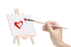 Mano con un pennello e una pittura di un cuore Fotografia Stock