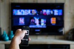 Mano con un teledirigido Cuál está en la TV, resbalando con películas del en de los apps en su televisión imagenes de archivo