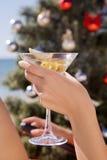 Mano con un vidrio de martini en la Navidad Imagen de archivo libre de regalías