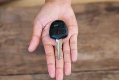 Mano con una chiave dell'automobile su fondo di legno Fotografia Stock