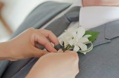 Mano con una flor en el traje Imagen de archivo