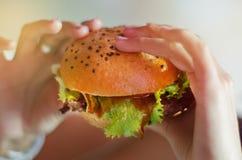 Mano con una hamburguesa sabrosa con lechuga fotos de archivo libres de regalías