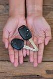 Mano con una llave del coche en el fondo de madera Imagen de archivo libre de regalías