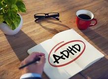Mano con una nota y una sola palabra ADHD imagen de archivo
