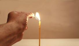 Mano con una partita e una candela Fotografie Stock Libere da Diritti