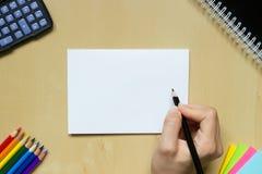 Mano con una penna su uno scrittorio Fotografia Stock