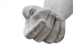 Mano con una piedra en un fondo blanco Fotografía de archivo libre de regalías