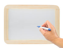 Mano con una pluma en el whiteboard de madera Fotografía de archivo libre de regalías