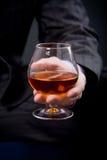 Mano con vetro del cognac Fotografia Stock Libera da Diritti