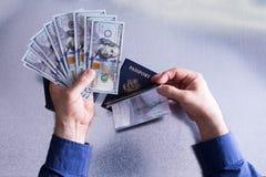 Mano conceptual que sostiene billetes de dólar y el pasaporte Foto de archivo