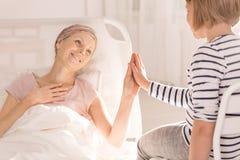 Mano conmovedora del ` s del niño de la mujer del cáncer Foto de archivo libre de regalías