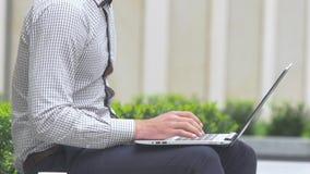 Mano cosechada del hombre que sostiene el teléfono móvil mientras que mecanografía en el ordenador portátil almacen de video
