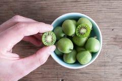 Mano cosechada que escoge la fruta de kiwi o la baya resistente del kiwi del cuenco de cerámica en la tabla imágenes de archivo libres de regalías