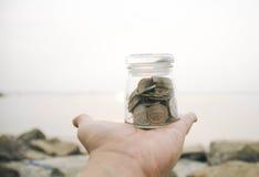 Mano cosechada que sostiene el tarro de cristal transparente con la moneda fondo de la falta de definición en la playa Imágenes de archivo libres de regalías
