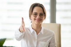 Mano d'estensione sorridente della donna di affari per la stretta di mano che esamina Ca immagini stock libere da diritti