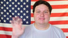 Mano d'ondeggiamento del giovane sui precedenti di una bandiera di U.S.A. stock footage