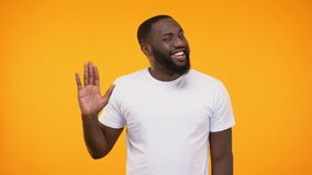 Mano d'ondeggiamento del giovane uomo di colore affabile cordiale, isolato su fondo giallo stock footage