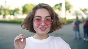 Mano d'ondeggiamento dell'attrice e sorridere nella fucilazione della pubblicità nel parco di estate archivi video