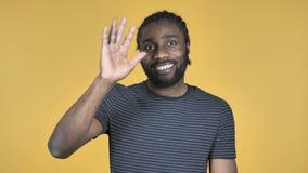 Mano d'ondeggiamento dell'uomo africano casuale da dare il benvenuto a isolato su fondo giallo video d archivio