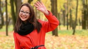 Mano d'ondeggiamento della bella giovane ragazza coreana agli amici video d archivio