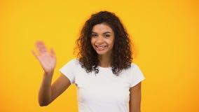 Mano d'ondeggiamento della ragazza afroamericana amichevole e ciao dire alla macchina fotografica, dante il benvenuto archivi video